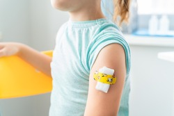 Vaccination of little girl in doctor's office.Kids funny adhesive plaster,gauze napkin.Sits on chair.Vaccine for covid-19 coronavirus,flu,infectious diseases.Injection.Clinical trials for human,child.