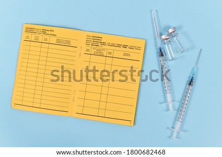 Vaccine concept with syringes, vials and empty yellow international certificate of vaccination with German and English text on blue background
