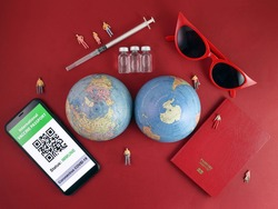 Vaccine passport smartphone app red sunglass world atlas globe map north south pole on red paper background world travel tour vacation mini human figures medical needle syringe bottle