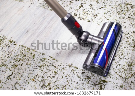 Vacuum cleaner on the floor. House cleaning concept. Before and after cleaning. Dirty and cleaned area. Housekeeping. Modern vacuum cleaner while vacuuming. Cleaning service Stockfoto ©
