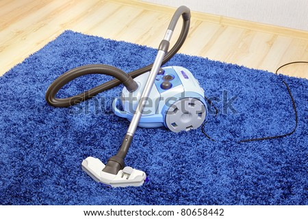 Vacuum cleaner stand  on blue carpet