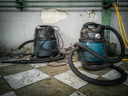 Vacuum Cleaners after used place on dirty floor at car washing service station