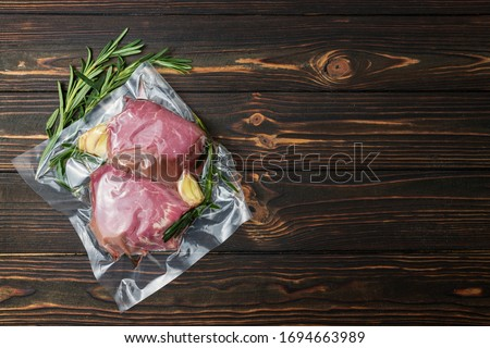 Vacuum-packed meat, on a wooden board, steak. Top view. Foto stock ©