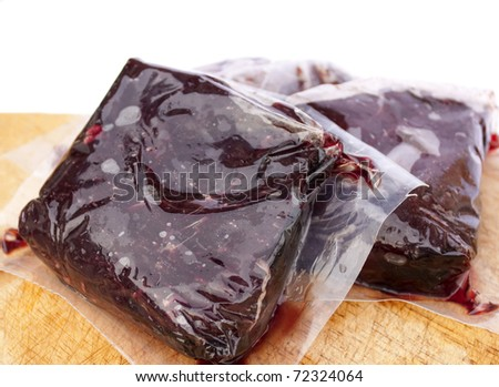 Vacuum sealed whale meat on a wooden board with white background.