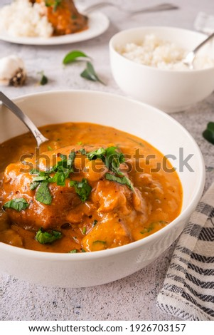 Vadouvan French-Style Curry Chicken and Cardamom. Stew with rice and fresh parsley. Curry leaves, turmeric, cloves, cumin, cardamom, garlic, brown mustard, smoked pepper Foto stock ©