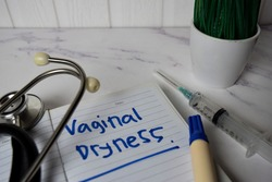 Vaginal Dryness write on a book and keyword isolated on Office Desk. Healthcare/Medical Concept