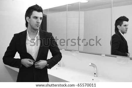 Vain business man checking his looks in the mirror