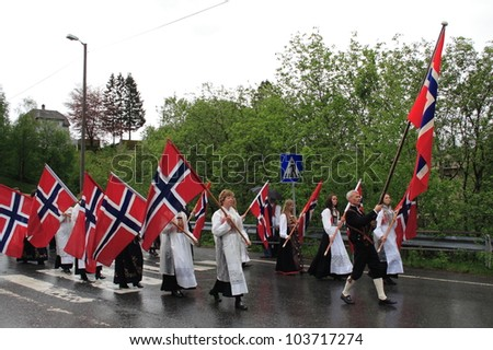 VAKSDAL, NORWAY - MAY 17: Flag bearers dressed in traditional costumes carry flags as they lead a Norwegian National Day parade through the village of Vaksdal on 17 May 2011.