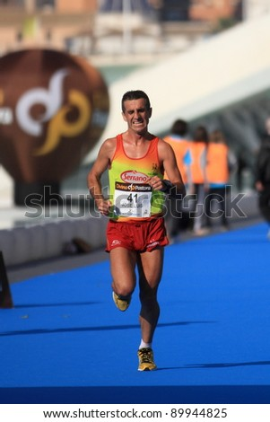 VALENCIA - NOVEMBER 27: Jose Luis (number 41) finalizing the mens marathon at finish line in Valencias Marathon on November 27, 2011 in Valencia, Spain - stock photo
