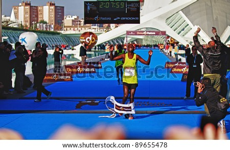 VALENCIA - NOVEMBER 27: kosgei (number 8) winning the mens marathon race at finish line with 2:07:09 time on chrono in Valencias Marathon on November 27, 2011 in Valencia, Spain