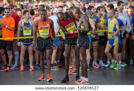 VALENCIA - NOVEMBER 18: Nathaniel Kipkosgei (number 2, 11th place men) prepares his friend number at starting line of mens maraton, in Valencias marathon on November 18, 2012 in Valencia, Spain