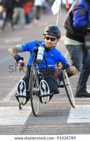 VALENCIA - NOVEMBER 27: Unidentified handicapped wheel chair hand-biker participating in Valencias Marathon behind runners on November 27, 2011 in Valencia, Spain