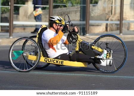 VALENCIA - NOVEMBER 27: Unidentified handicapped wheel chair hand-biker participating in Valencias Marathon behind runners on November 27, 2011 in Valencia, Spain
