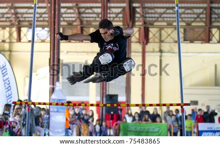 VALENCIA, SPAIN - APRIL 16: Front view of amateur Inline Skater doing acrobatics and jumping over a bar in the roller skate exhibition day celebrated each year on April 16, 2011 in Valencia, Spain