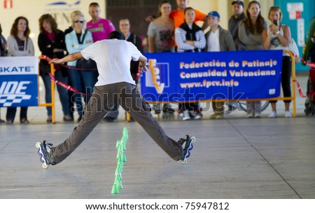 VALENCIA, SPAIN - APRIL 16: Rear view of an unidentified amateur Inline Skater doing acrobatics with cones in the roller skate exhibition day celebrated each year on April 16, 2011 in Valencia, Spain