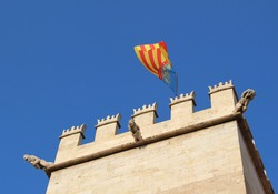 Valencia Spain College of high silk art looking up at tower with gargoyles and community of Valencia flag