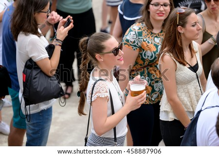 VALENCIA, SPAIN - JUN 11: A woman drinks a beer at Festival de les Arts on June 11, 2016 in Valencia, Spain. #458887906