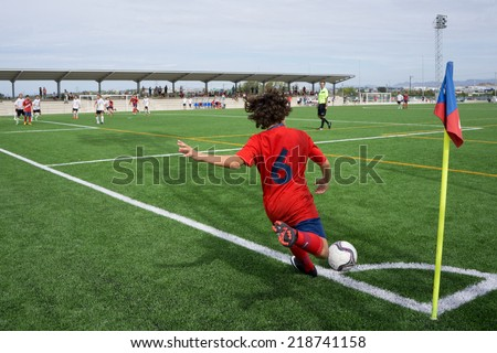 VALENCIA, SPAIN - SEPTEMBER 20, 2014: An unknown youth player taking a corner kick during a youth soccer match. Soccer is the most popular sport in Spain.