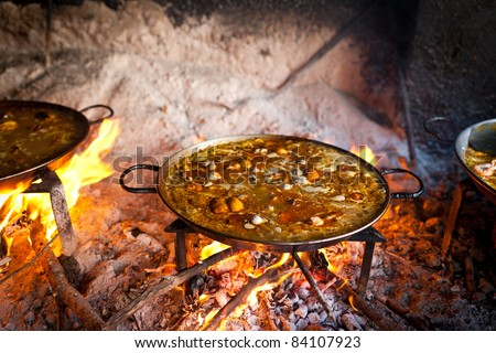 Valencian paella cooking on log fire in local Spainish village