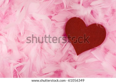 Valentin love theme - red fabric heart lying in pink feathers background.