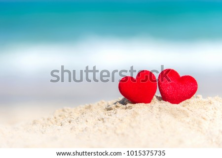 Valentine and Marry Concept.  Two red hearts couple lovers for married on the sand summer beach, blue background.
