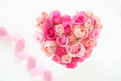 Valentine background.  Heart shaped  bouquet of beautiful pink rose flowers with pink ribbon