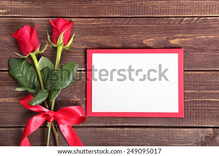 Valentine background of red roses and blank white card with red envelope on wood. Space for copy.