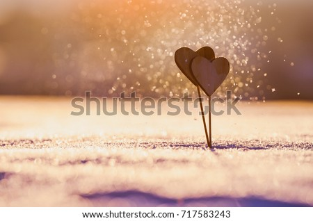 Valentine background - two wooden hearts in beautiful snowflakes in the air #717583243