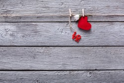 Valentine background with red paper heart and love word on clothespins on rustic wood planks. Happy lovers day card mockup, copy space