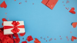 Valentine background with wrapped present and papper hearts from above. Open box filled with rose leaves with envelope on blue backdrop. Flat lay composition of love symbols with copy space.