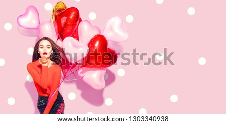 Valentine Beauty girl with colorful air balloons laughing, on pink background. Beautiful Happy Young woman. holiday party. Joyful model having fun, playing and celebrating with red color balloon #1303340938