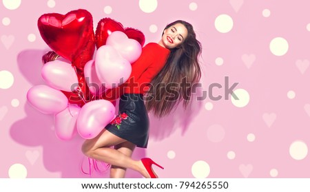 Valentine Beauty girl with red and pink air balloons laughing, on pink polka dots background. Beautiful Happy Young woman. holiday party. Joyful model posing, having fun, celebrating  Valentine's Day