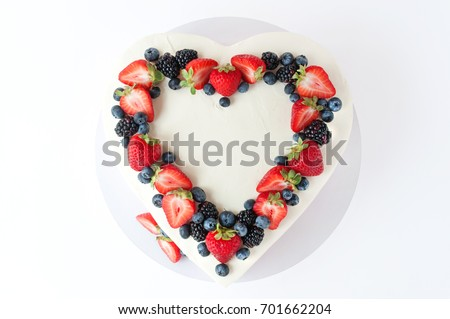 Valentine cake in form of heart with whipped pink cream, decorated with strawberries, blueberries and blackberry on white background. Picture for a menu or a confectionery catalog. Top view.