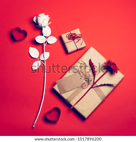 Valentine composition on the red background with flowers, hearts and cartoon packages. Valentine's day. Love concept. #1017896200