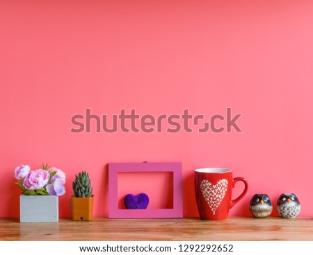 Valentine  concept  setting  with  rose,cactus,wooden  picture  frame,heart,cup  and  simulated  owl  on  pink  background