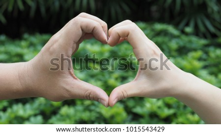 Valentine concept with heart shaped hand sign of Asian lover. Love hand sign, hand language on blurry green nature background. (selective focus) #1015543429