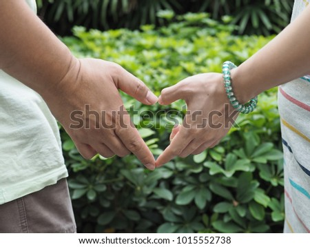 Valentine concept with heart shaped hand sign of lovely husband and pregnant wife. Love hand sign, hand language on blurry green nature background. (selective focus) #1015552738
