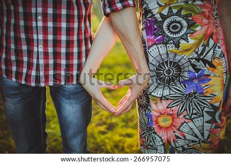 Valentine Couple in love showing Heart with their fingers.