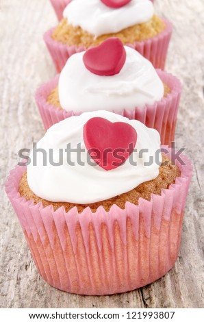 valentine cupcake with white icing and red hearts