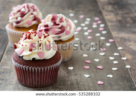 Valentine cupcakes decorated with sweet hearts on wooden table\n\n