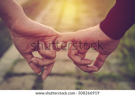 Photo of Valentine day background. Happy couple holding hands together as forever love. Vintage filter.