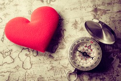 Valentine day background. Old compass on vintage map with red heart. Retro filter. Direction to real love of your heart concept.