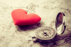 Valentine day background.Old compass on vintage map with red heart. Retro filter. Direction to real love of your heart concept.