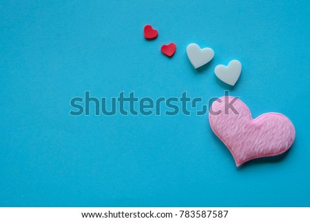Valentine day concept. Cute pink heart shape made from cotton and smaller hearts are on the bright blue background, love theme. Copy space background #783587587