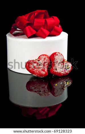Valentine day concept: white gift-box with red bow and two hearts on black background with reflection