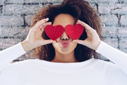 Valentine Day Love Beautiful concept . Happy African American girl holding two hearts on her eyes.