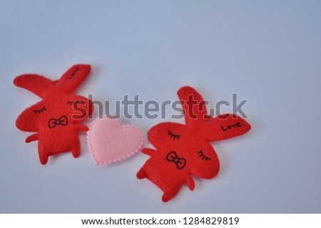 Valentine Day: Two red rabbits crafts holding a heart shaped piece of paper on a white background #1284829819