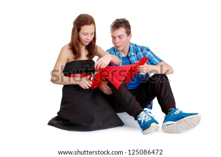 Valentine day. Two teenagers cutting valentine heart out of red paper. Isolated on white background
