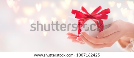 Valentine gift. Beauty Woman hands holding Gift box with red bow over holiday  background with glowing hearts bokeh, close-up. pastel colors. Wide angle format backdrop #1007162425