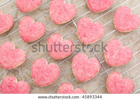 Valentine heart cookies with red sugar sprinkles cooling on a rack, full frame, horizontal